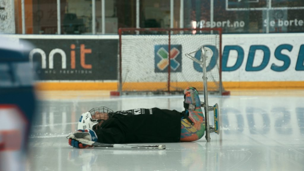 One player on the para ice hockey team lying on his back on the ice.