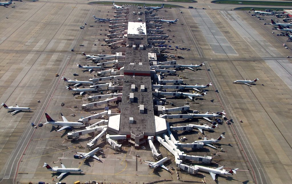 Many planes crowding an airport runway.