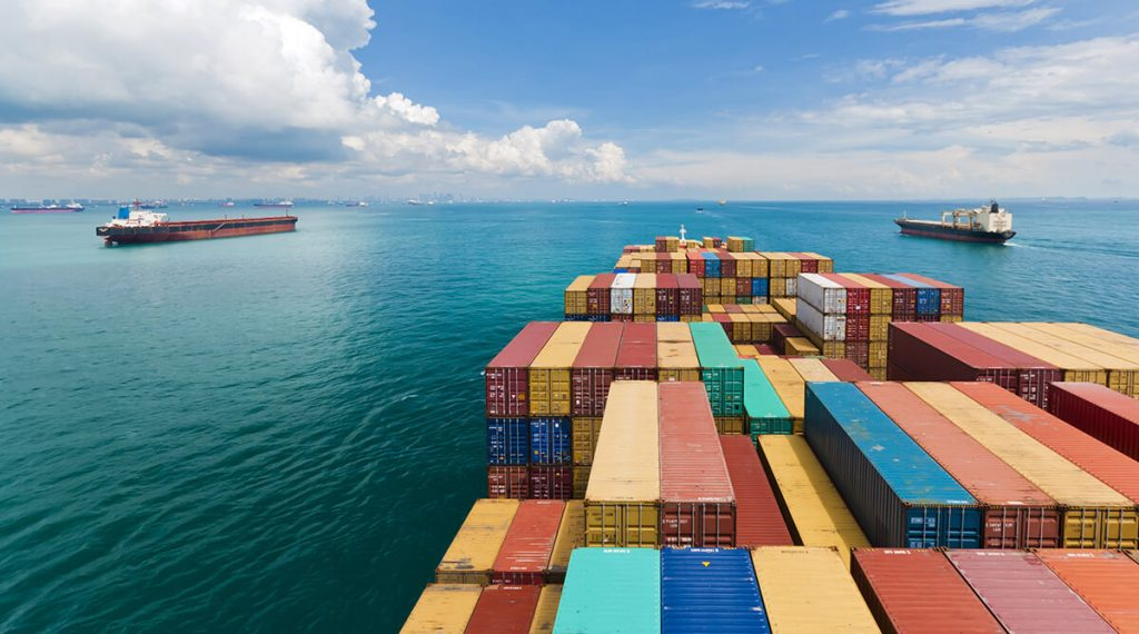 Global shipping cargo containers on a vessel out at sea.