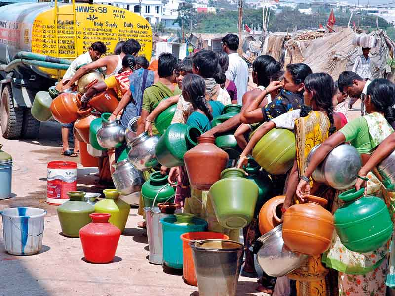 People in India line up to fill their jars with drinking water.