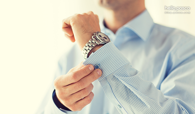 손목시계를 차고 셔츠 소매 단추를 잠그는 모습
