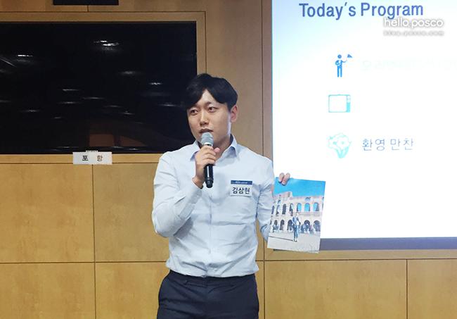 김삼현 신입사원이 자신의 이탈리아 콜로세움 사진을 들고 설명하는 모습