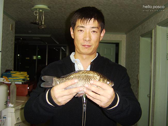 잡은 물고기를 들고 찍은 사진