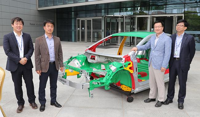이미지 제공 - 한국지엠 자동차의 차체가 있고 그앞에 네명의 직원이 서있다.