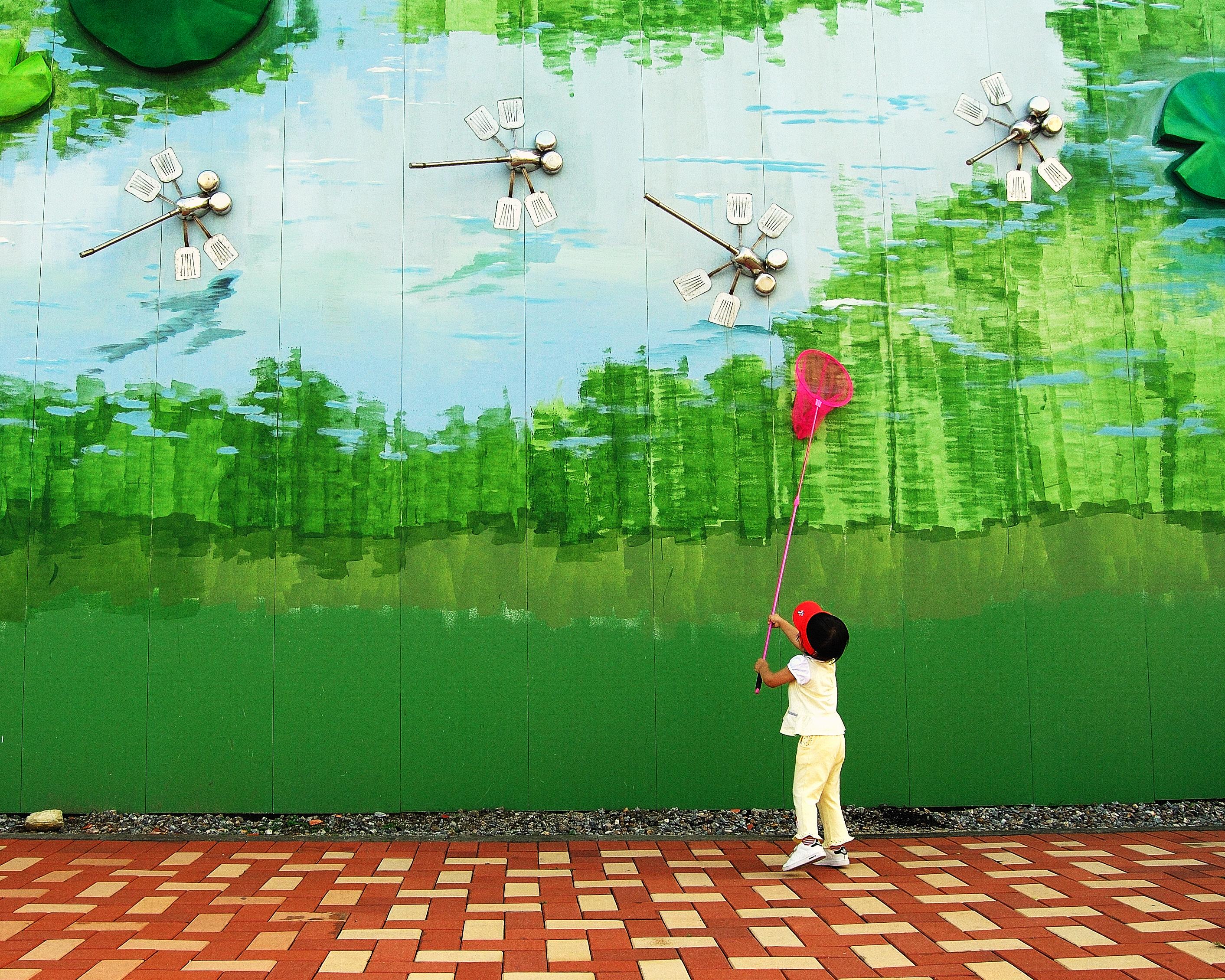 어린아이가 잠자리 채로 철로 만든 잠자리를 잡는 장면을 재미있게 표현한 작품