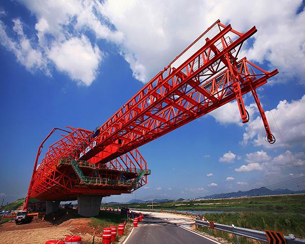 대형 철 구조물로 교량을 건설하는 장면 빨간색