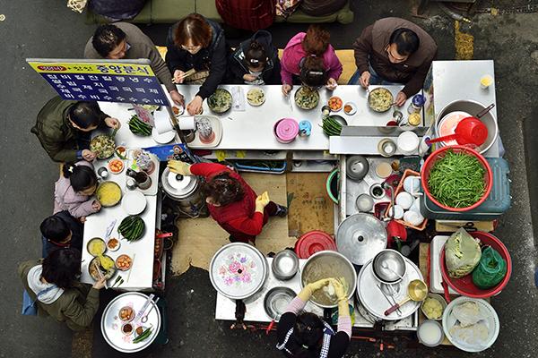 시장 분식점의 쟁반, 그릇, 수저 등 다양한 식기들부터 남녀노소의 사람들이 식사하는 모습