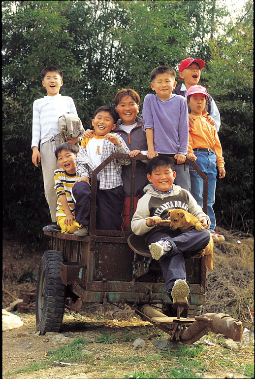 철로 만든 농기구 위로 올라탄 아이들의 모습에서 장난스러운 개구장이들
