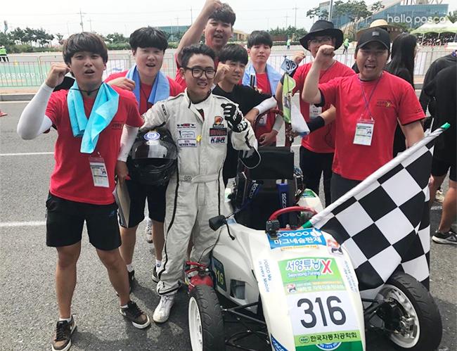 '2017 대학생 자작자동차대회'에 출전한 서영대 튜닝엑스팀이 포스코 마그네슘 판재를 적용해 제작한 자동차로 EV(전기차) 부문 우승을 차지했다. (화이팅을하고 있는 단체사진)
