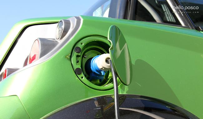 초록색 자동차의 열린 주유구에 주유가 되고 있는 모습