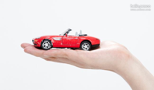 자동차 경량화 (손위에 올려진 빨간 장난감 자동차)