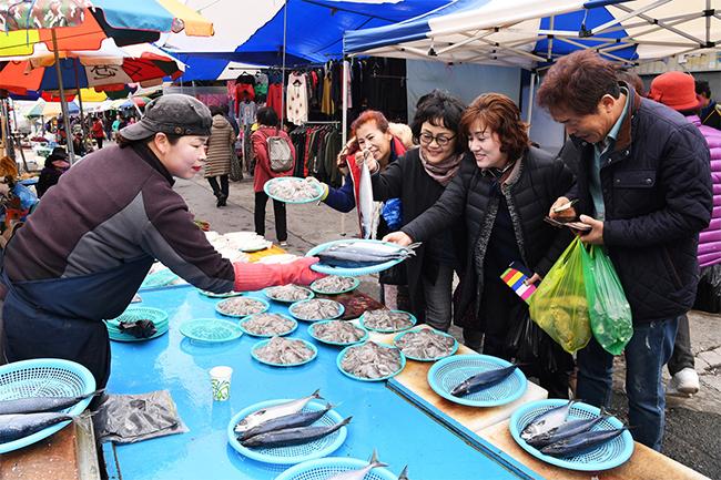 광양제철소 직원 부인회가 3월 16일 열린 광양 5일장을 찾아 해산물을 구입하고 있다.