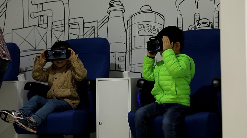 제품전시관 1층에 있는 vr체험을 하는 2명의 어린이.