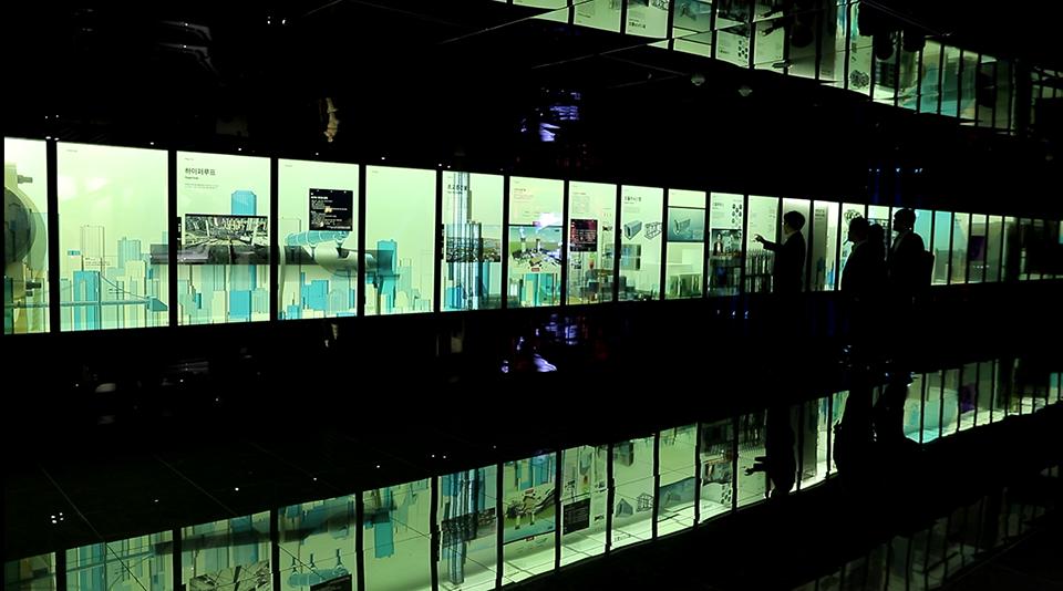 제품전시관 2층에 전시품을 보고 있는 3명의 사람이 있다.