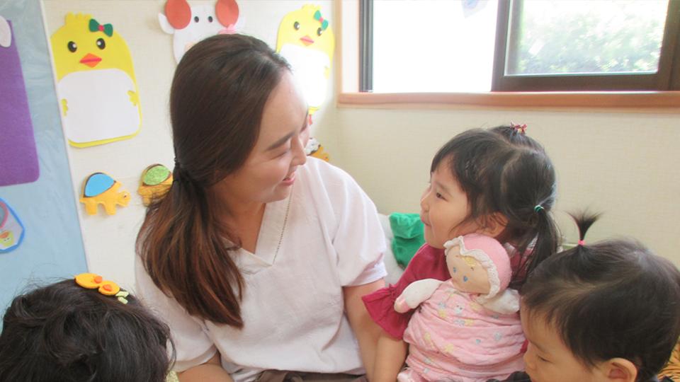 광양 포스코어린이집 나비반 김공은 교사와 아이가 마주보며 웃고있는 모습.