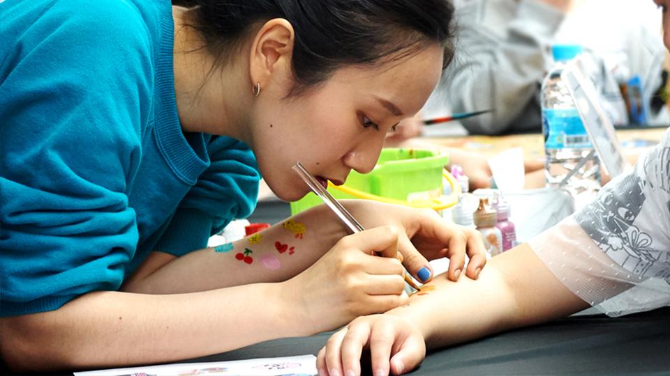 페이스 페인팅 도우미로 참가한 이솜이씨가 부스를 찾은 어린이의 팔에 그림을 그려주고 있다.