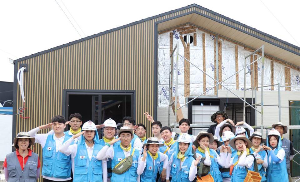 포스코가 소외계층에게 기부하는 스틸하우스 건축 봉사에 참여한 비욘드 11기 단원들이 스틸하우스 앞에서 단체로 포즈를 취하고 있다.