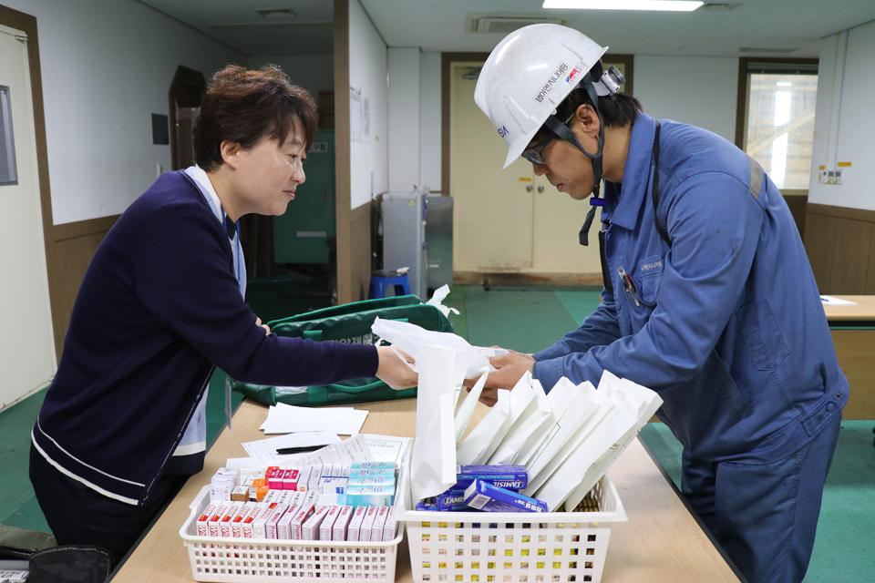 건강증진섹션 진료팀 간호사가 작업자의 질병, 혈압, 건강상태에 맞춘 전문의약품을 나눠주고 있다.