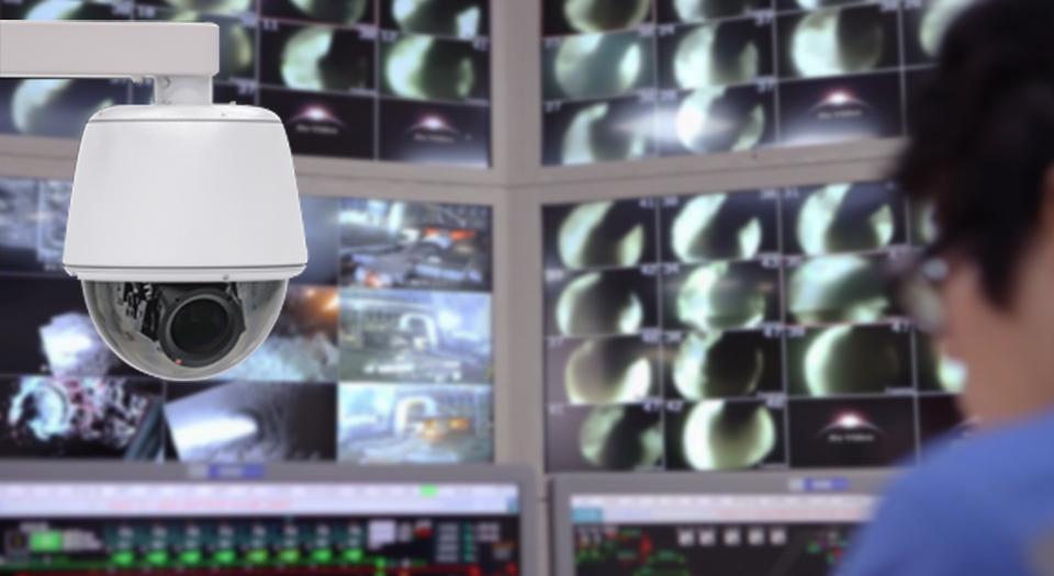 스마트 CCTV와 뒤편으로 여러 대의 CCTV 모니터가 보인다.