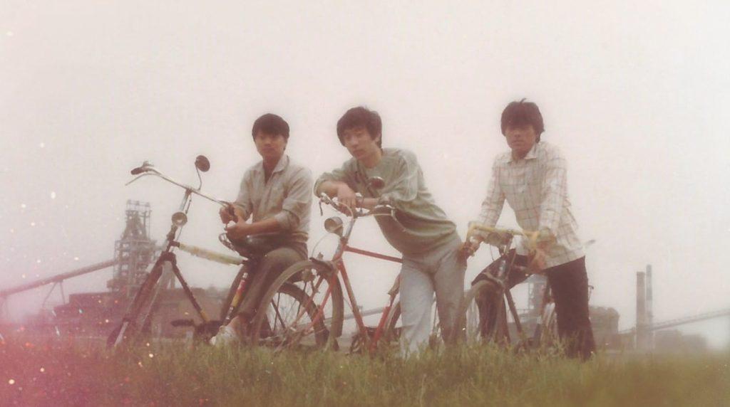 배동석 명장 신입시절 모습.  남자 셋이 세 대의 자전거에 각각 타거나 기대어 있다.
