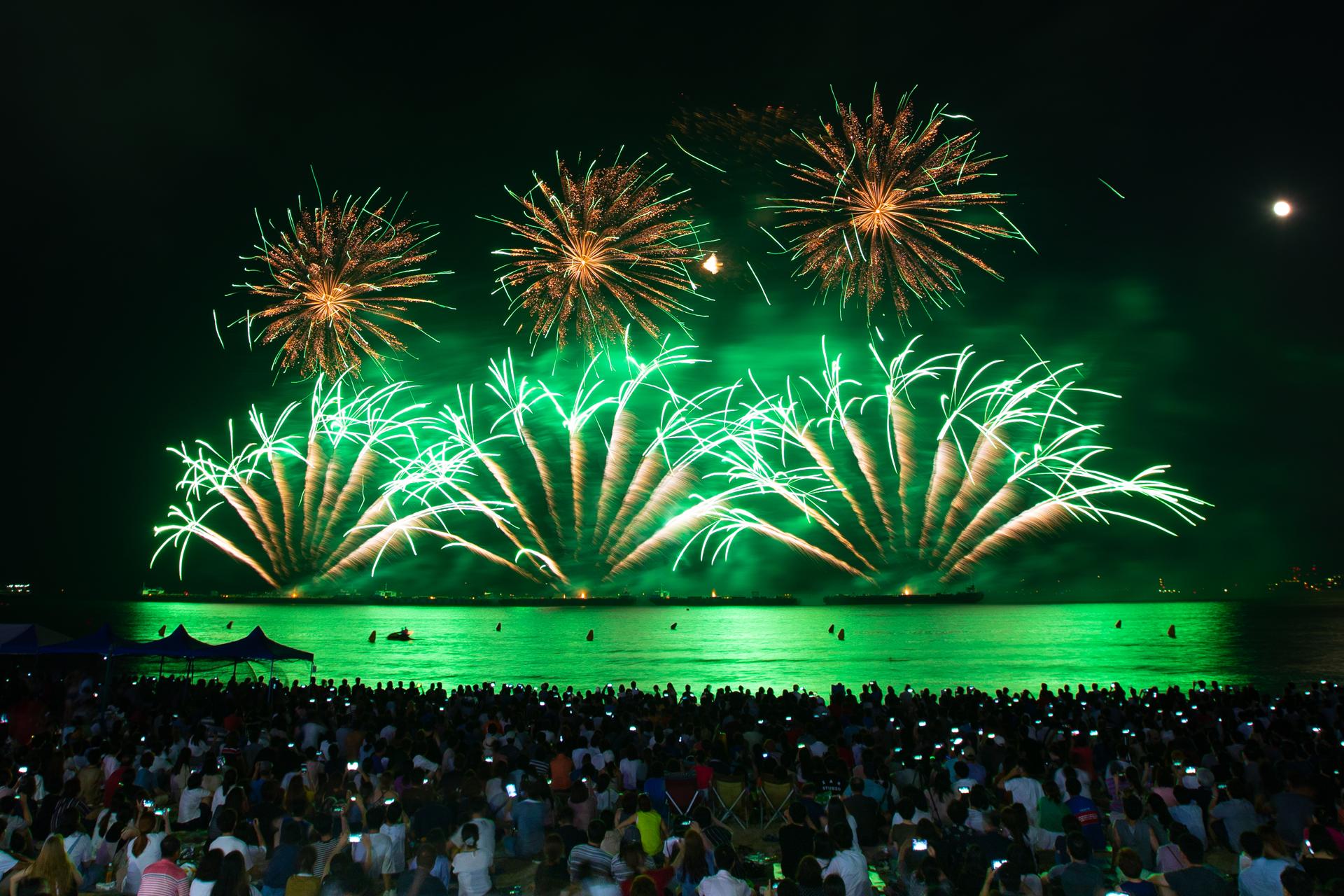 불꽃쇼 한국한화 원 모양의 볼꽃 세 개 아래 부채꼴 모양의 불꽃 세 개가 하늘에 수놓여있다. 수많은 시민들이 불꽃을 구경하고 있다.