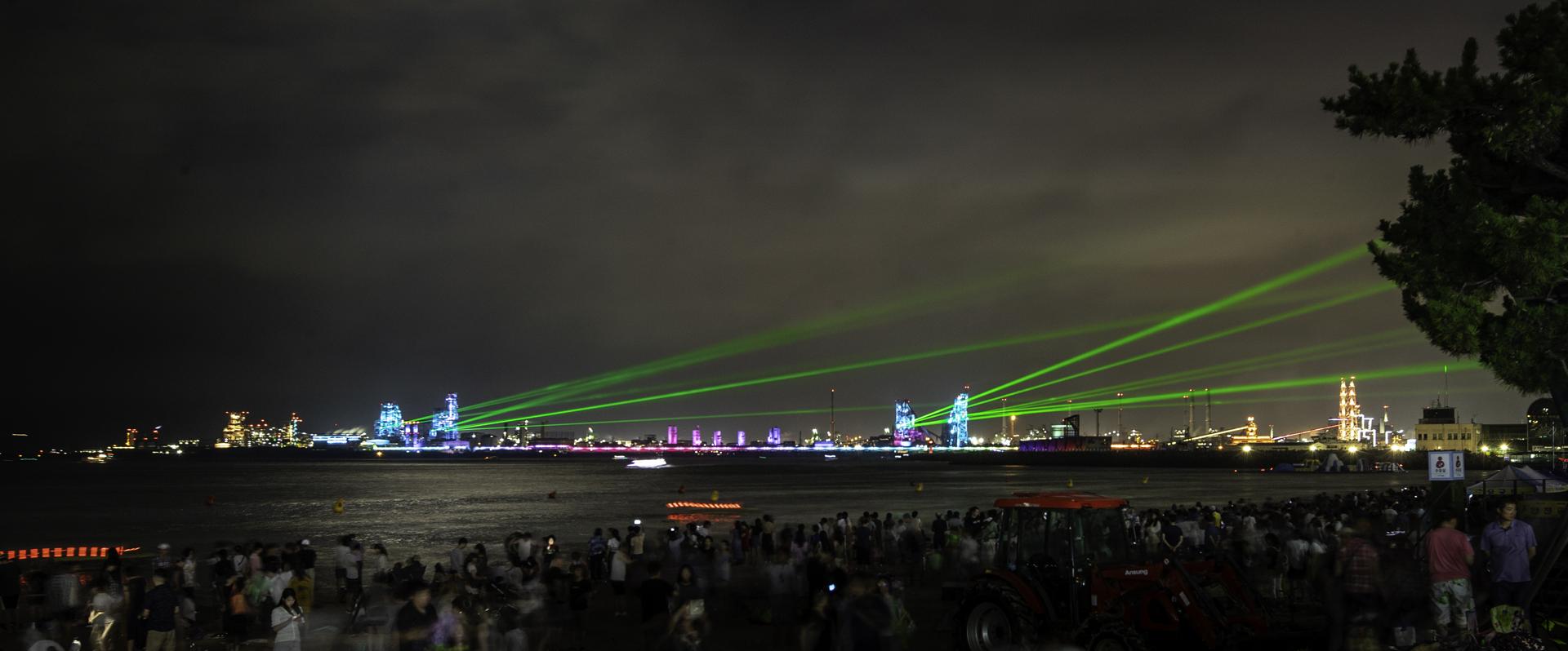 2018 포항 국제 불빛 축제 반짝반짝 퐝퐝쇼1 수많은 인파로부터 멀리 떨어진 곳에서 직사광선이 쏟아져 나오고 있다.