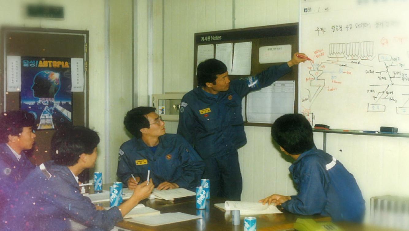 이경재 명장 신입사원시절 회의 모습. 사원 네 명이 테이블에 앉아 한 사원이 화이트보드를 가리키며 설명하는 것을 보고 있다.