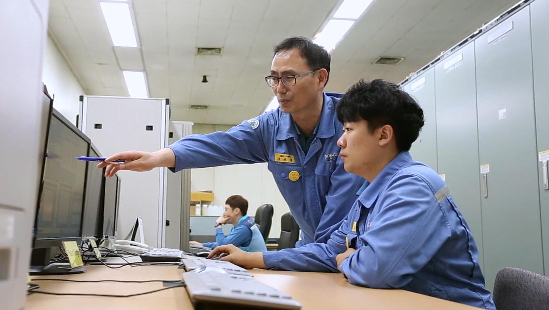 이경재 명장이 직원에게 컴퓨터 모니터를 가리키며 업무를 설명하고 있다.