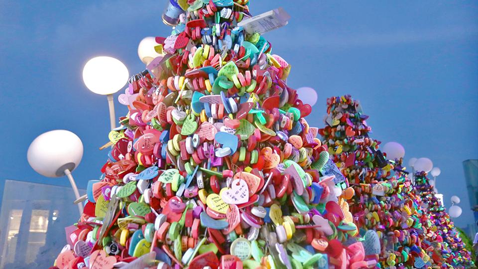 알록달록한 사랑의 자물쇠들이 쌓여 고깔 모양을 이루고 있다.