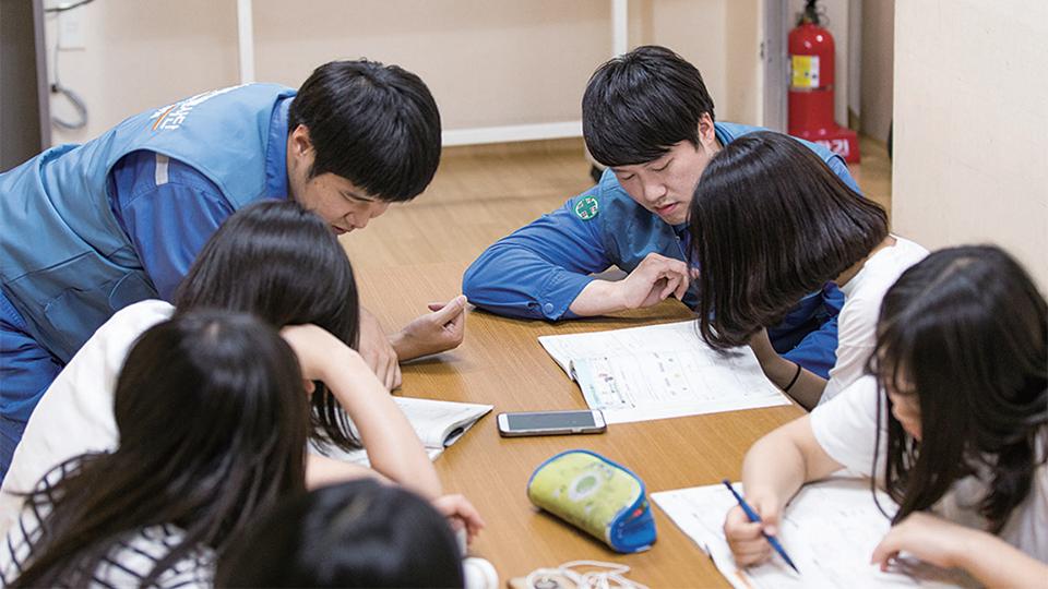 젊은 엔지니어들이 아이들 공부를 가르쳐 주고 있다.