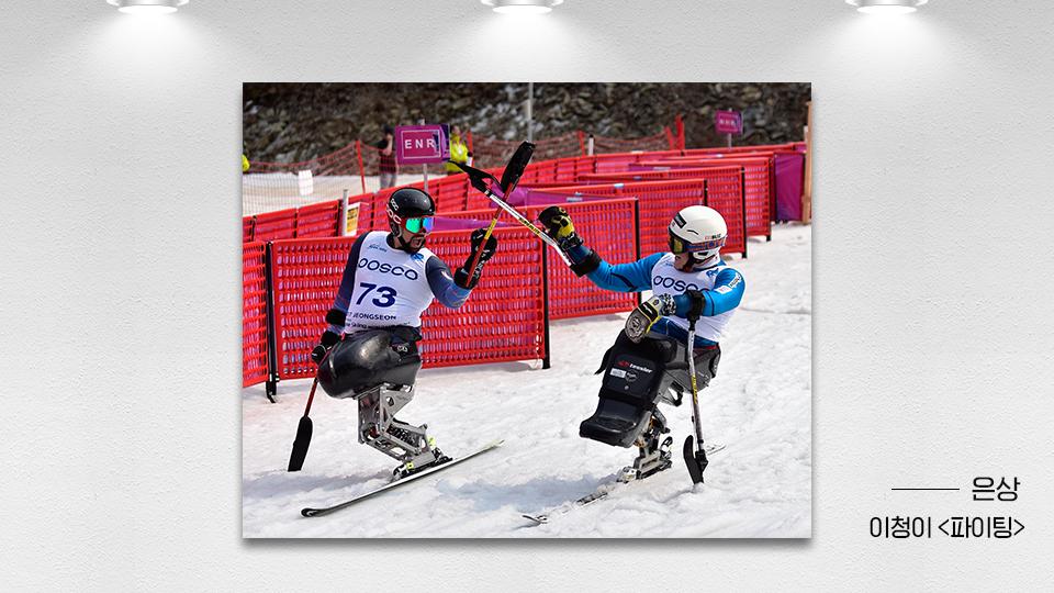 19회 철강사진 공모전 은상작 이청이 파이팅. 평창 동계패럴림픽에 출전한 선수 두 명이 각각 왼손 오른손에 든 장비로 X자 모양을 만들고 있다.