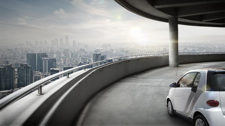 빌딩으로 가득찬 도시가 내려다 보이는 주차 타워에 전기차 SUV가 세워져 있다.