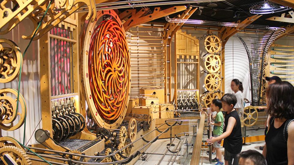 굴러가는 쇠구슬로 에너지 만드는 체험 기구를 아이들이 작동해보고 있다.
