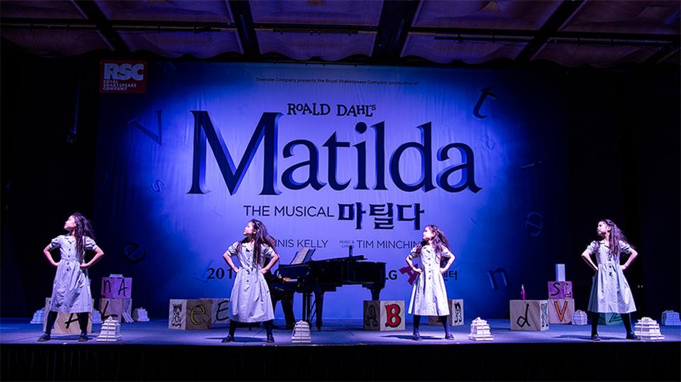뮤지컬 마틸다 공연 모습. 네 명의 여자 아이가 일정한 간격을 두고 서서 허리에 양손을 올린 채 오른쪽 위를 올려다보고 있다.