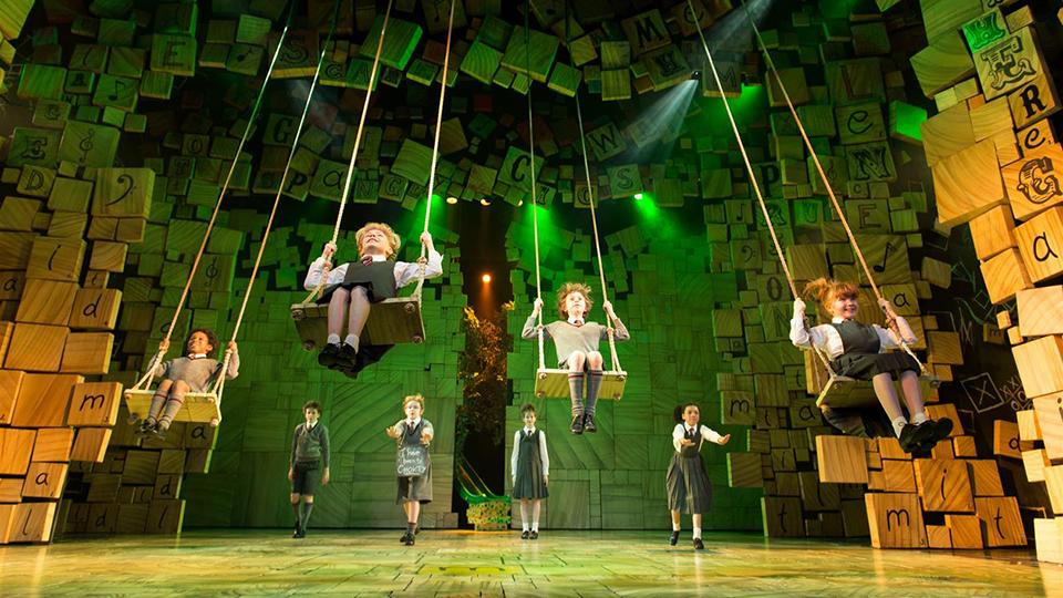 뮤지컬 마틸다 공연 모습. 네 명의 아이들이 천장에 메달린 그네를 타고 뒤에서 네 명의 아이가 서 있다.