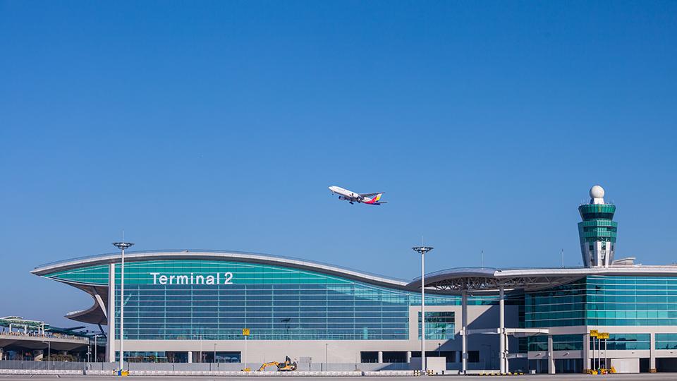 인천공항 제2여객터미널 위로 비행기가 날아가고 있다.