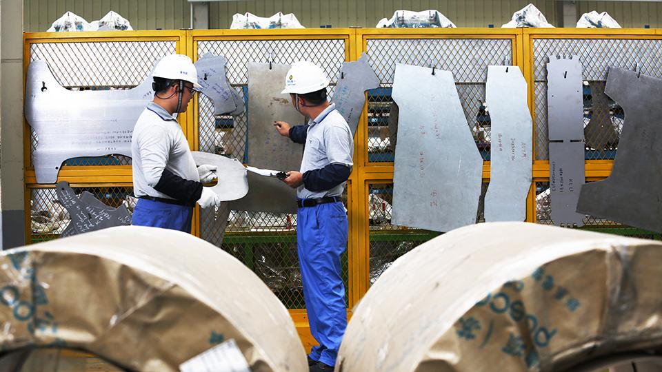 공장 근무자들이 금속 업무에 관해 논의하고 있는 모습.