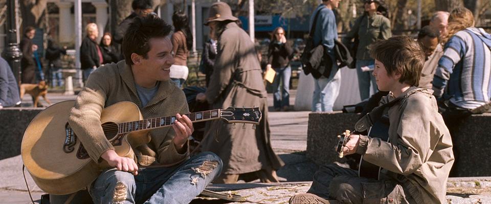 영화 어거스트 러쉬의 스틸 이미지 (출처:영화사 그램) 노래 부르던 남자가 아이와 기타를 매고 이야기 나누는 모습