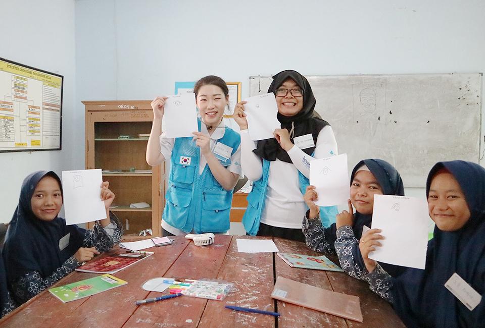 교실에서 한국인 여성 봉사단원, 현지인 봉사단원과 검은색 히잡을 쓴 여학생들이 그림을 그린 종이를 들고 웃고 있다