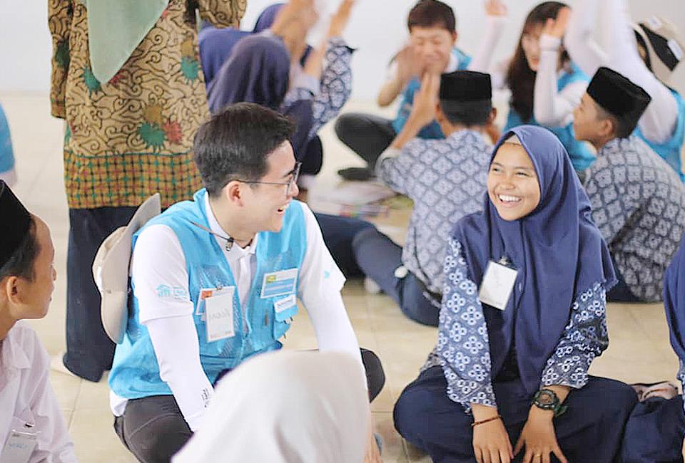 남자 봉사단원과 히잡을 두른 여학생이 활짝 웃고 있는 사진