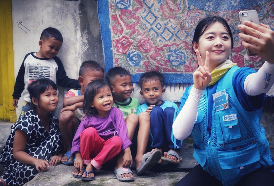 인도네시아 현지 아이들과 여성봉사단원이 함께 핸드폰으로 사진을 찍고 있다