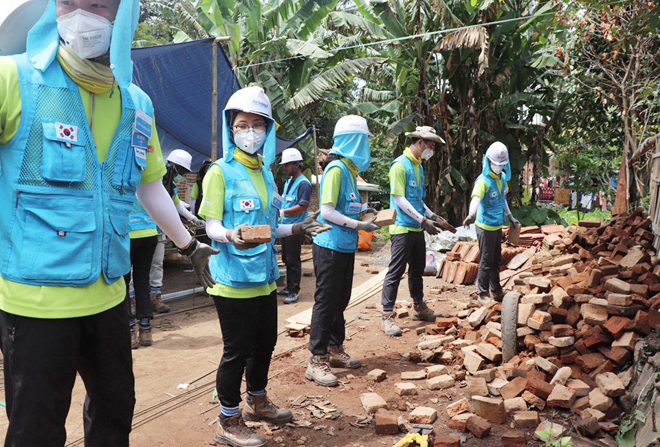 포스코 비욘드 봉사단 인도네시아 건축 봉사- 흰색 안전모 연두색 반팔티 하늘색 조끼를 입은 봉사단이 한줄로 서서 벽돌을 나르는 사진