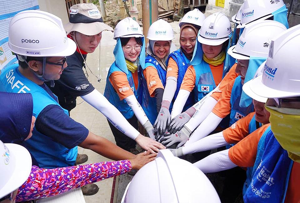 포스코 비욘드 봉사단 인도네시아 건축 봉사- 흰색 안전모 오렌지색 반팔티 하늘색 조끼를 입은 봉사단이 파이팅 하는 사진