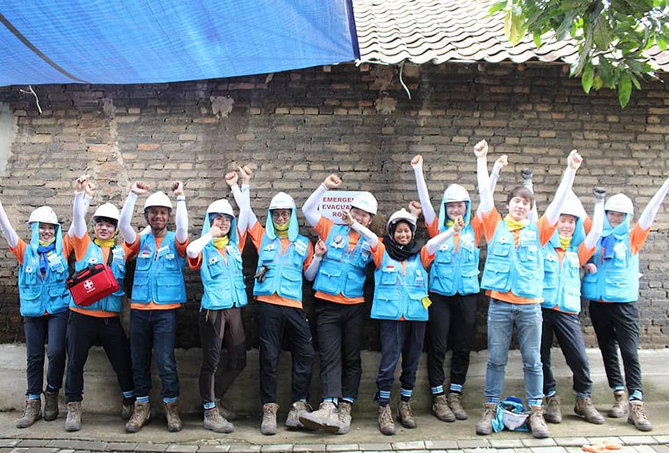 포스코 비욘드 봉사단원들이 인도네시아에서 벽을 배경으로 양손을 높이 들고 파이팅하는 사진