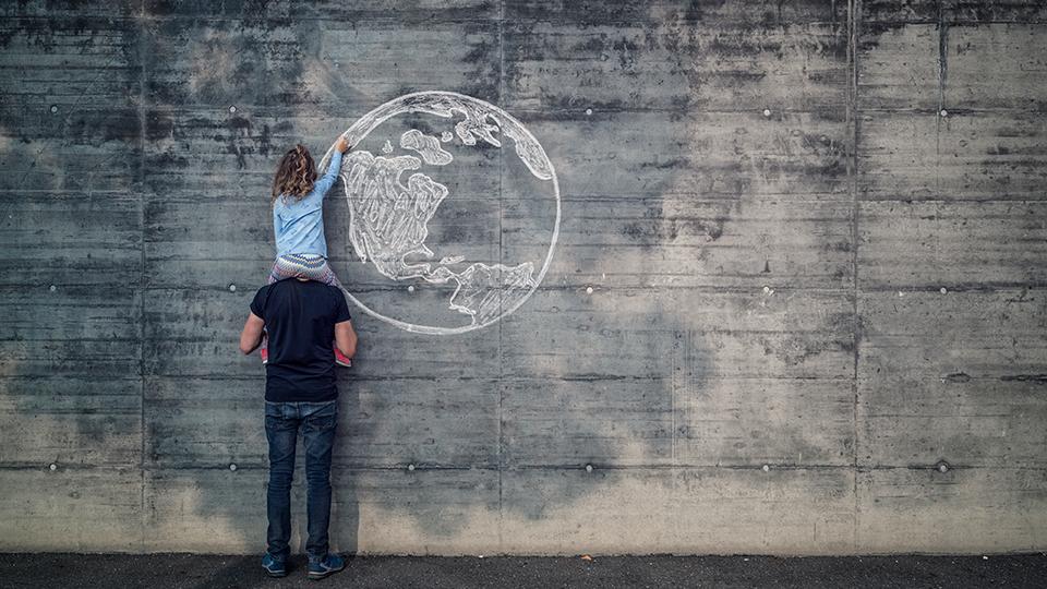 지구벽화- 성인남자의 목말을 탄 여자 아이가 시멘트 벽 위에 흰색으로 지구를 그리고 있는 사진