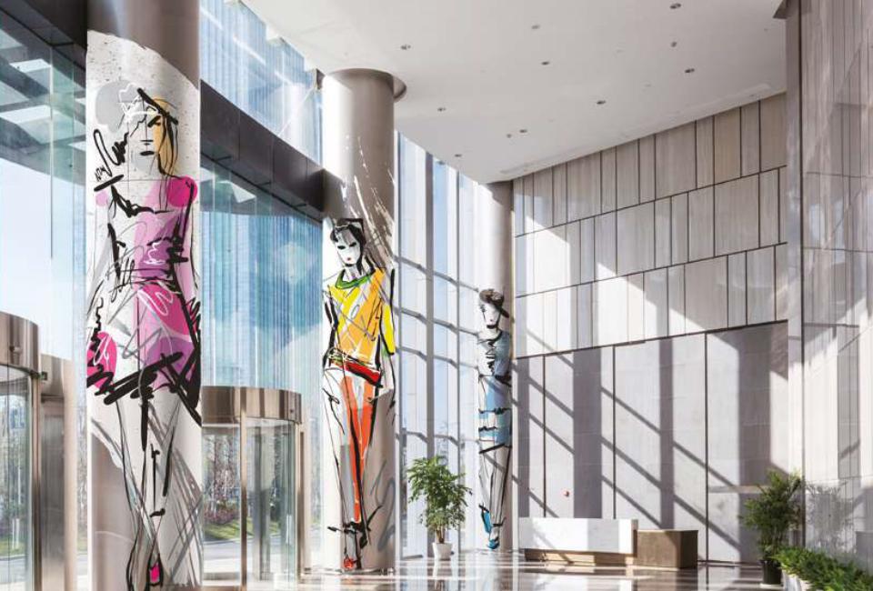 포스아트(PosART)- 햇빛이 들어오는 건물 로비 높은 기둥에 포스아트로 제작된 패션일러스트가 프린팅 되어있는 이미지