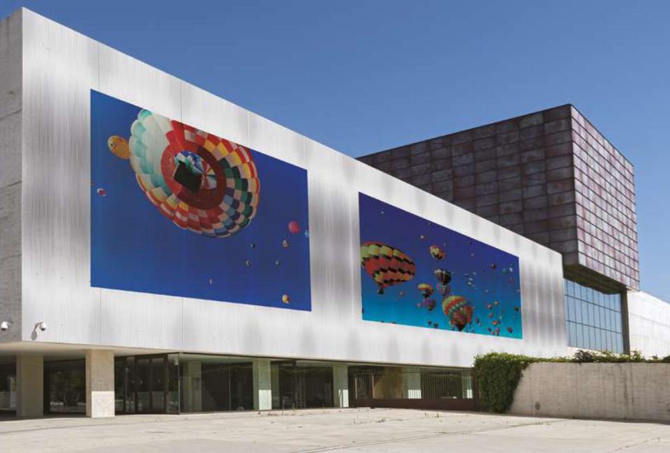 직사각형의 멋지 건물 외벽에 다양한 색상의 열기구가 프린팅 되어있는 이미지