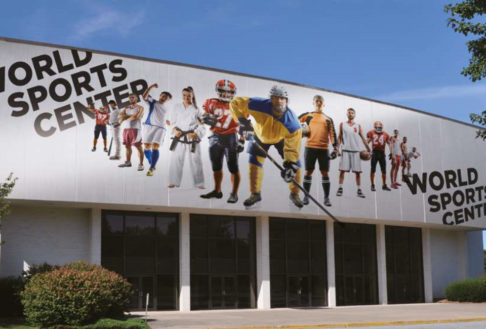 포스아트(PosART)- 체육관 건물 외벽에 WORLD SPORTS CENTER 하키선수 중심으로 럭비, 축구, 농구, 태권도, 축구, 럭비, 농구, 야구 선수들의 이미지가 삼각형으로 되어있다 WORLD SPORTS CENTER