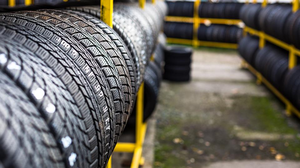 타이어 사진-노란색 선반에 여러개의 타이어가 정리되어 있다