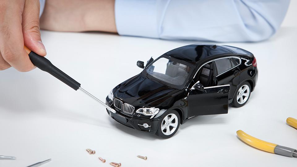 자동차 정비- 화면 중앙에 검정색 모형 자동차를 검정색 손잡이의 드라이버을 가지고 가리키고 있다. 그 앞에 나사들과 공구 손잡이가 있다.